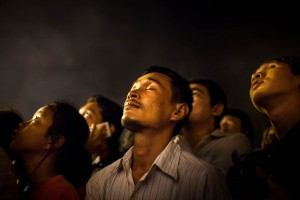 A man closes his eyes in prayer as hundreds of people stare at the moon looking for a resemblance of their King. Phnom Penh, Cambodia.
