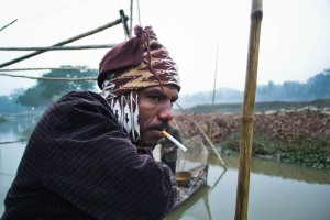 Ranjeet's partner smokes a cigarette on the early hours of the morning. During winter, the fishermen spend up to 8 hours on the boat without proper winter clothes.