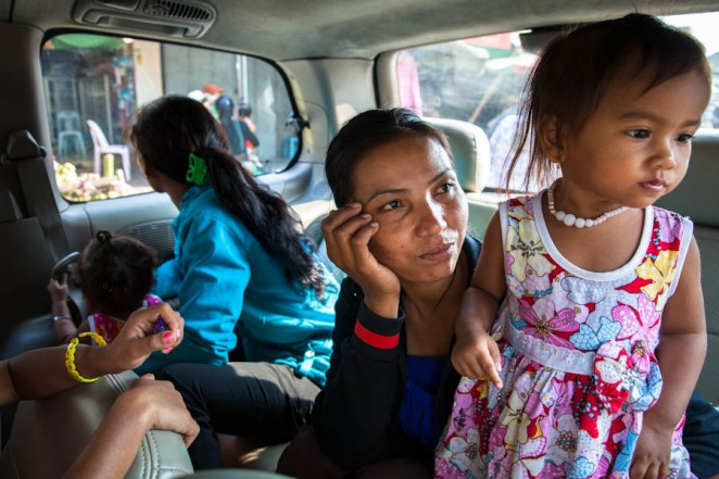 Phorn Sreoun's wife, Phat Phin and daughter look out the car's window on their way to Correctional Centre 1. Four days before, they made the exact trip expecting their husbands to be released along Mam Sonando. Mar 19 2013 ©Erika Pineros