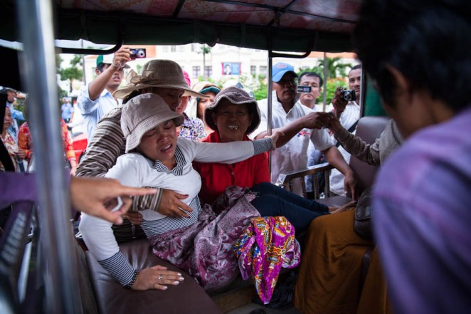 Hek Chan Reaksmey, 33, who was 2 and half months pregnant, is taken by fellow demonstrators to the hospital after she started bleeding as consequence to clashes with the police. Jul. 01, 2013. ©Erika Pineros