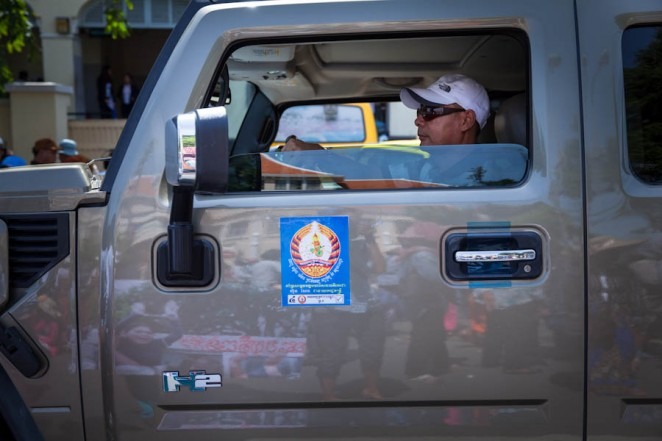 A Hummer H2 with stickers of the ruling party CPP drives past a demonstration in front of City Hall in Phnom Penh. Jul. 02, 2013. ©Erika Pineros