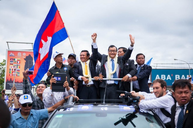 Cambodian opposition leaders Kem Sokha and Sam Rainsy greet supporters along their way from Phnom Penh's airport. Jul. 19, 2013 ©Erika Pineros
