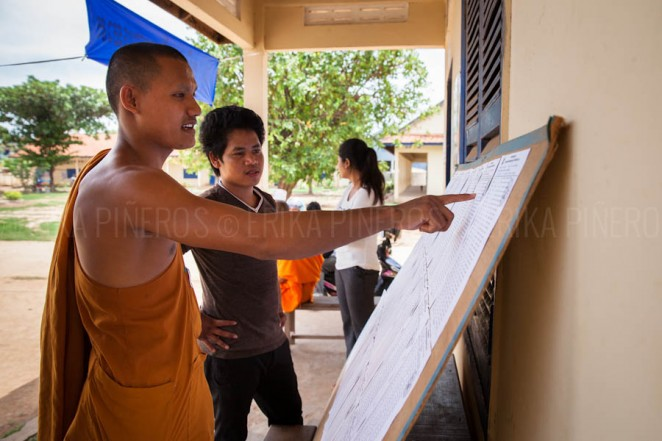 A Buddhist monk checks for his name at a voting poll near his pagoda in rural Cambodia. Jul. 27, 2013. ©Erika Pineros