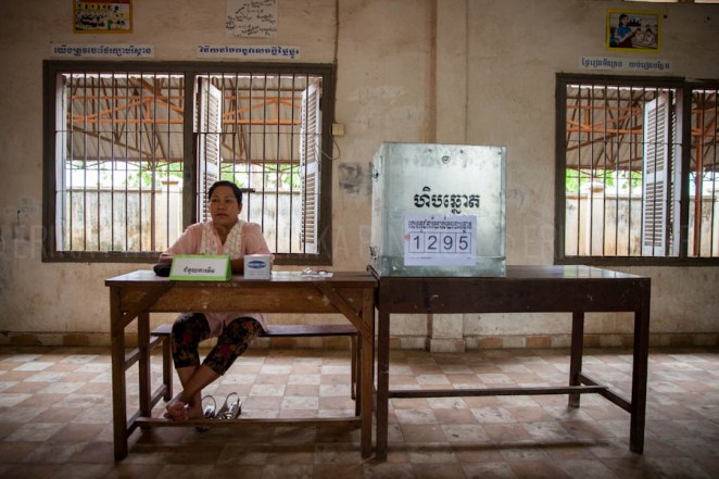 A woman sits by a ballot box at Wat Phnom Bunrang High School voting station in Phnom Penh. Jul. 28, 2013 ©Erika Pineros