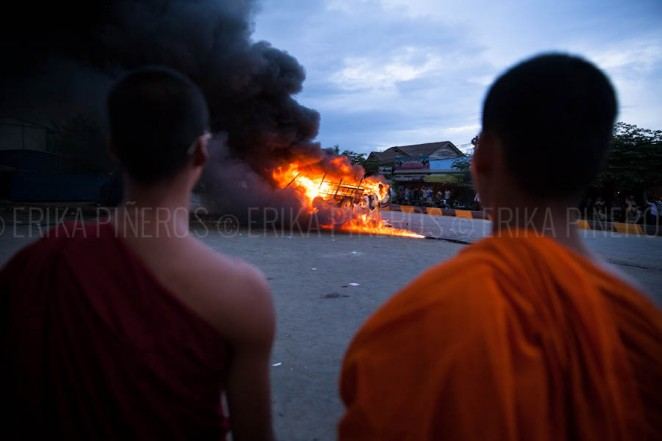 Monks watch burning police cars after mobs attacked them at Stung Meanchey District in Phnom Penh. Jul. 28, 2013 ©Erika Pineros