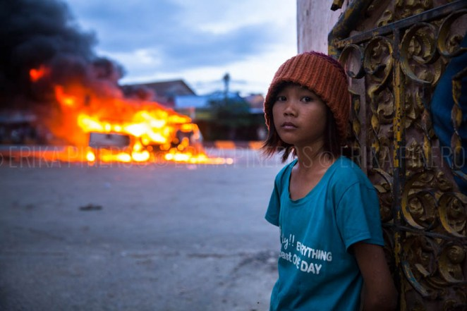 A girl stands by Stung Meanchey's pagoda's gates as two police cars burn in the background. Mobs later on attacked a man they thought to be Vietnamese. Jul. 28, 2013 ©Erika Pineros