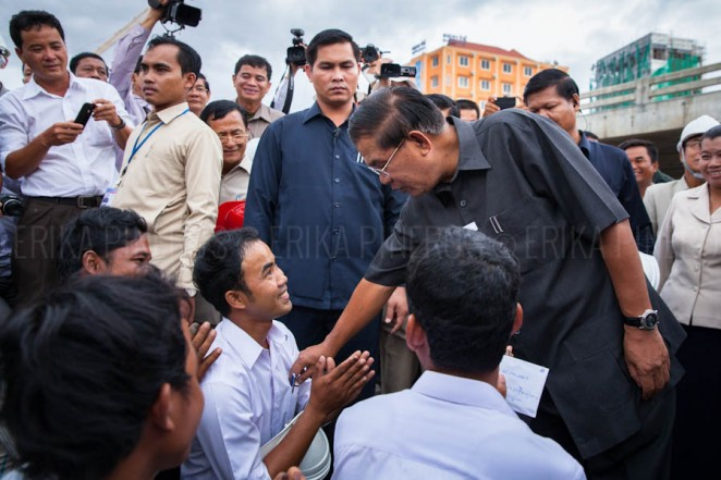 Cambodian Prime Minister Hun Sen distributes money to workers during his visit to Stung Meanchey's bridge on his first appearance after elections. Phnom Penh. Jul. 31, 2013 ©Erika Pineros