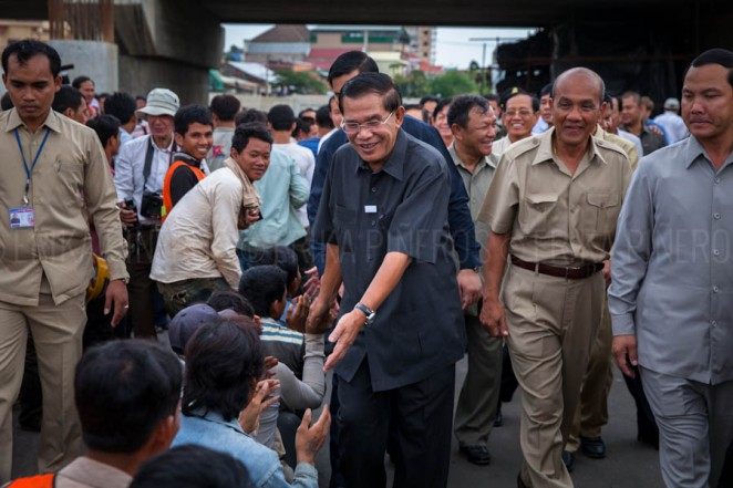 Cambodian Prime Minister Hun Sen distributes money to workers during his first visit to Stung Meanchey's bridge on his appearance after elections. Phnom Penh. Jul. 31, 2013 ©Erika Pineros