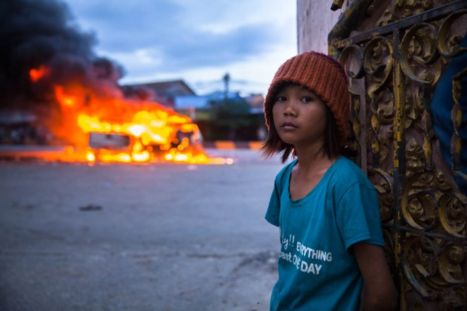 A girl stands by Stung Meanchey's pagoda's gates as two police cars burn in the background during post-election riots in Phnom Penh. Mobs later on attacked a man they thought to be Vietnamese. Phnom Penh, Cambodia. Jul. 28, 2013 ©Erika Pineros