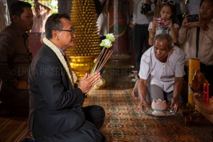Opposition leader Sam Rainsy prays during his visit to Wat Phnom. Apr. 30, 2014 ©Erika Pineros