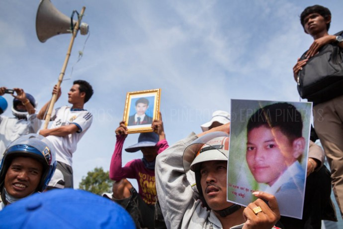 Demonstrators hold pictures of January's deadly clashes victims during a protests in front of Freedom Park on Labour Day in Phnom Penh. May 1, 2014 ©Erika Pineros