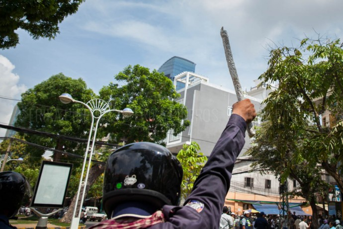 A policeman threatens civilians and media by raising a 'homemade' baton in the air. Police and thugs arbitrarily  attacked several people after Labour Day's demonstration at Phnom Penh's Freedom Park. May 1, 2014 ©Erika Pineros