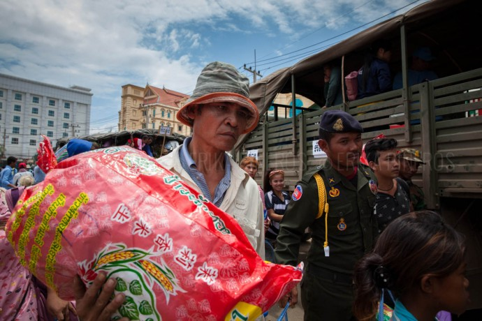 A man carries his belongings on his return to Cambodia. Daily, thousands of people continue to return from Thailand fleeing the Coup. June 17, 2014. Cambodia ©Erika Pineros