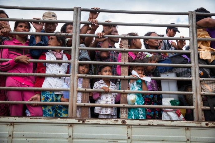 Cambodian workers and their families arrive by the hundreds in Thai trucks to the Cambodian border town of Poipet. June 17, 2014. Cambodia ©Erika Pineros