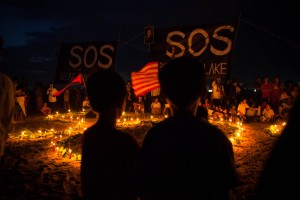 Children stand in front a huge SOS candlelit sign during a demonstration aimed to get attention from ASEAN leaders to land and other human rights issues in Cambodia.