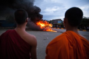 Monks watch burning police cars after mobs attacked them at Stung Meanchey District in Phnom Penh.