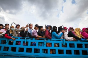 Garment factory workers pile up in trucks to make their daily journey to and from work. Kampong Speu, Cambodia.