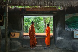 Cambodian Buddhist monks take a look inside one of the bear enclosures at Phnom Tamao Wildlife Rescue Center.