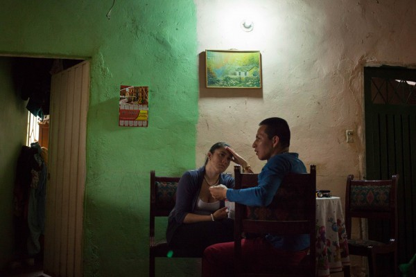 "Fabio, an ex-commander for the FARC, and his girlfriend Yisel talk after dinner during a visit to Camilo's house, a fellow demobilised from the ELN. ""I never had anything to do with the conflict in Colombia, until I met him. I've never had such a difficult relationship before, but I don't regret"", says Yisel. ""I asked the ACR for psychological support, but they didn't provide anything""."