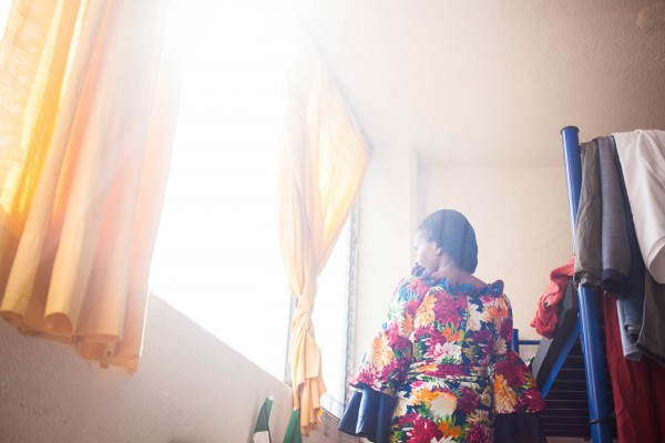 Aisha poses for a photo in one of the dresses she brought with her when she fled Congo.